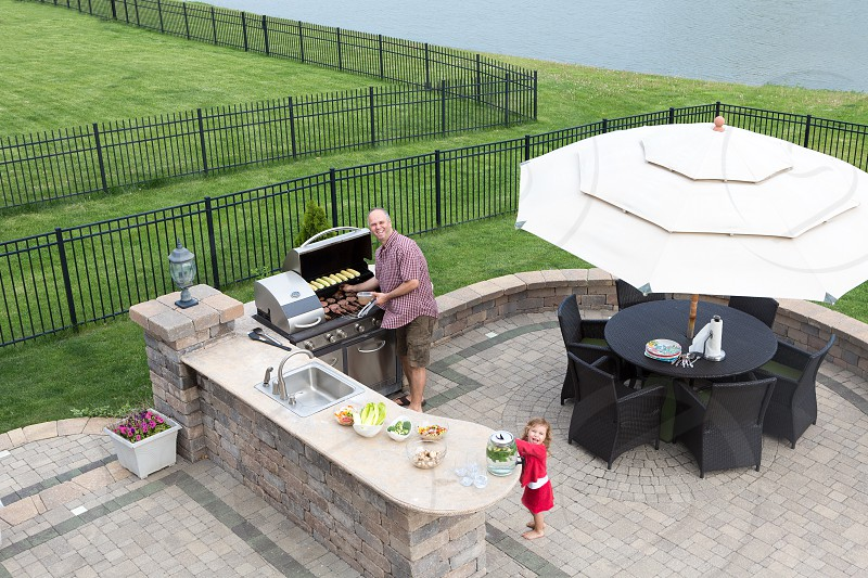 Father and daughter preparing a barbecue at an outdoor summer kitchen on a paved patio with a garden umbrella table and chairs as they grill the meat on the gas BBQ waiting for guests to arrive photo