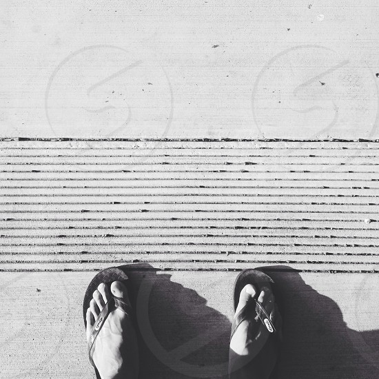 grayscale photo of person wearing pair of flip-flops photo