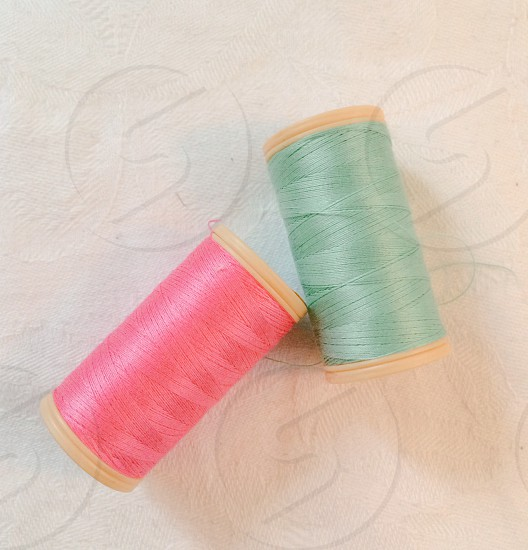 green and pink thread spool photo