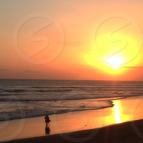 person walking on seashore golden hour photography photo
