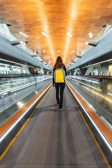DOHA QATAR - JANUARY 23 2019: One woman traveller with backpack go on moving walkway travolator in new Hamad International Airport. Back view photo
