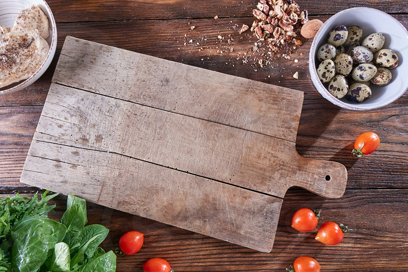 Fresh herbs nuts tomatoes and boiled meat on a wooden table with a kitchen board and copy space. Healthy salad products. Flat lay photo