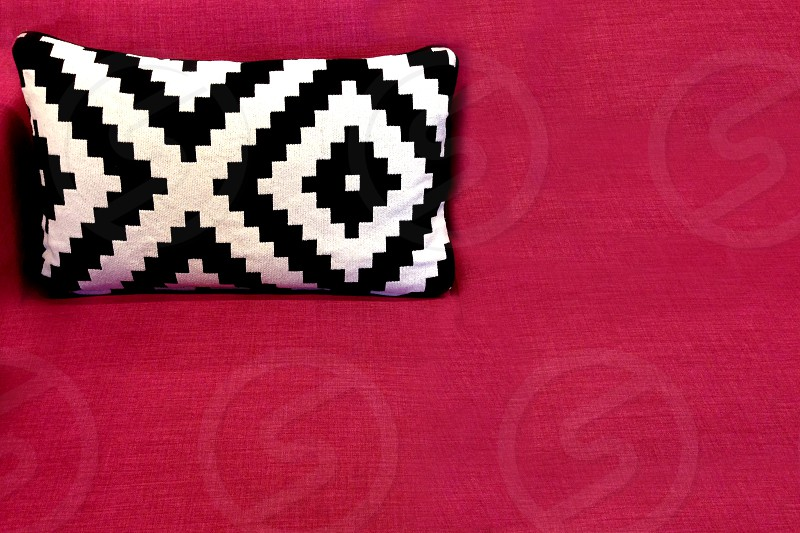 Black and white graphic designed pillow rests on a rose colored background photo