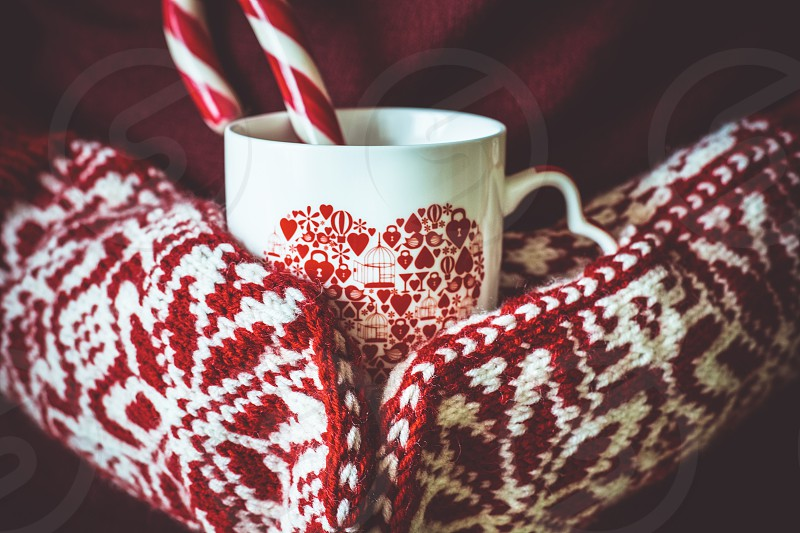 Hands in knitted gloves holding a cup of hot chocolate photo