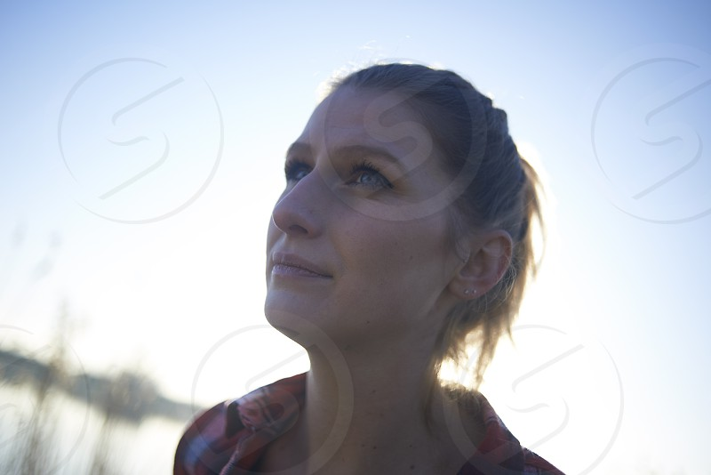 Portrait of a young caucasian woman with piercing blue eyes taken outdoors in winter sunshine near a lake photo