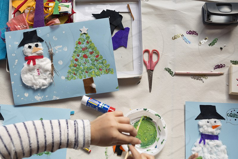 Hands of a 10 year old girl doing a Christmas craft. Horizontal shot photo