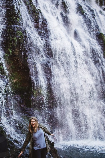 woman in grey cardigan standing beside waterfalls during daytime photo