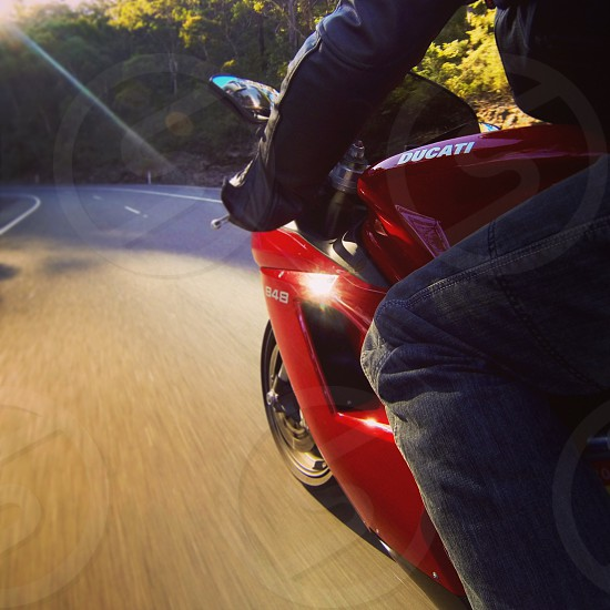 person riding red Ducati sport bike timelapse photo taken during daytime photo