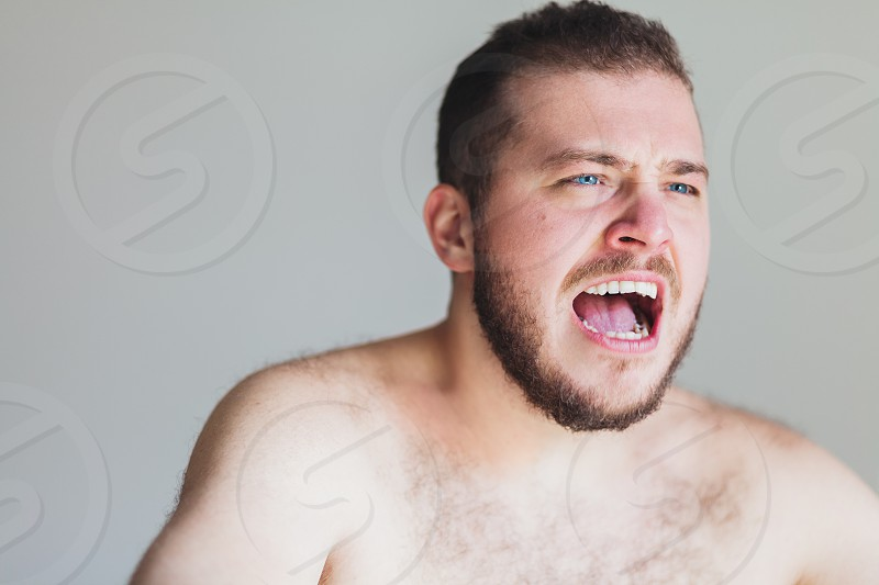 Young emotional man screaming in anger photo