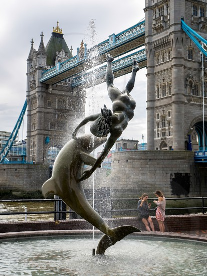 David Wayne Sculpture Girl with the Dolphin next to Tower Bridge in London photo