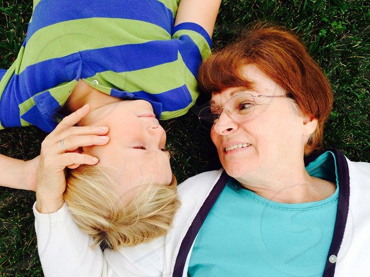 woman with boy lying on grass smiling photo