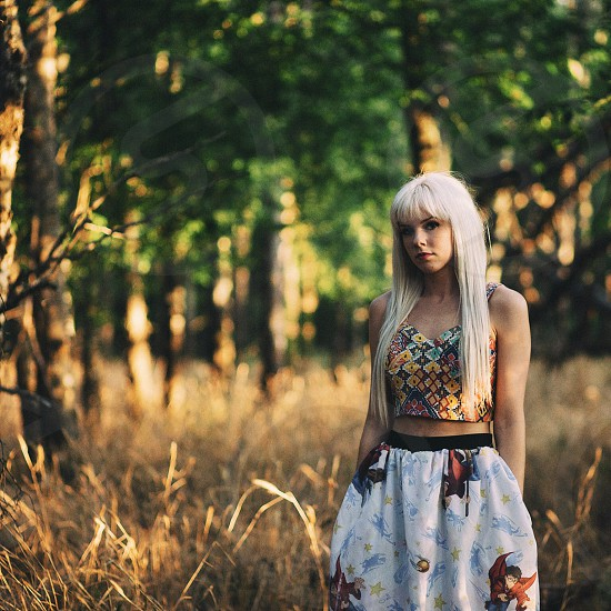 woman standing in a field near trees photo