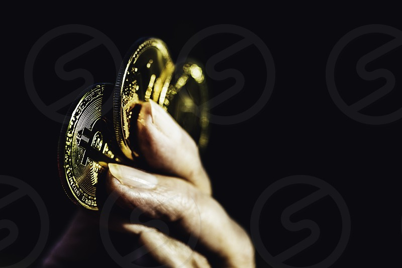 Female fingers hold gold bitcoins. Golden bitcoins in female hand. Close-up virtual currency bitcoin isolated on black background. Physical Bitcoin. Crypto currency trading concept. photo