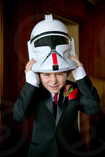 A young man wearing a tuxedo peeks out from under his stormtrooper mask. photo