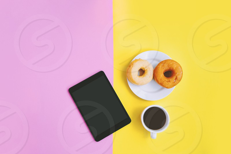 Coffee break relax concept A cup of black coffee donuts and tablet on yellow pink pastel background with copy space photo