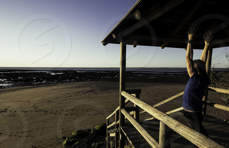 Young man practicing yoga on pier with Sanlucar de Barrameda beach in the background photo