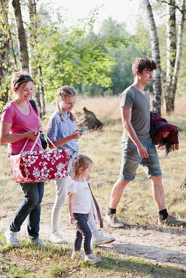 Happy family going on picnic  to forest on sunny day in the summertime photo