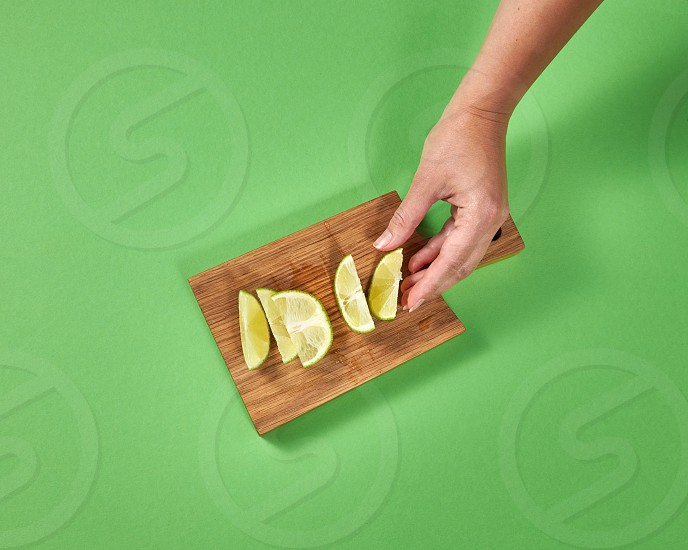 Organic natural fresh lime slices on a wooden board. Female hands takes a piece of lime for preparing homemade natural lemonade. Concept of healthy natural vegetarian food. photo