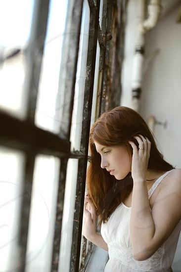 Beautiful red head woman gazing out window on rainy day photo
