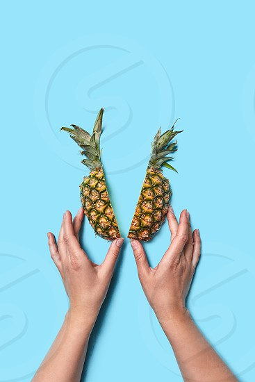 Girls hands hold halves of juicy pineapple on a blue background with space for text. Flat lay photo