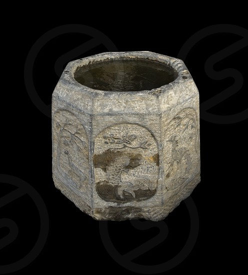 ancient stone bucket finely carved with iced water over black backgroungd photo