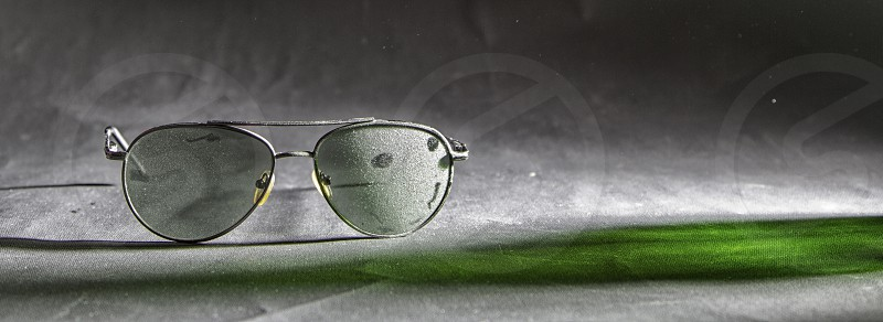 Sunglasses in the dust close-up with a shade of green photo