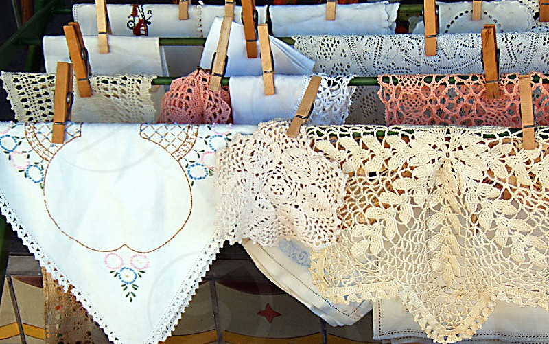 Vintage handkerchiefs and crocheted doilies are hung up with clothespins. photo