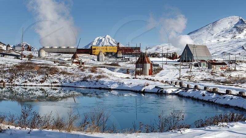 KAMCHATKA PENINSULA RUSSIA - OCT 22 2017: Winter panorama on Mutnovskaya Geothermal Power Station (Mutnovskaya GeoPP-1) Geotherm JSC (PJSC RusHydro) using geothermal energy to produce electricity. photo