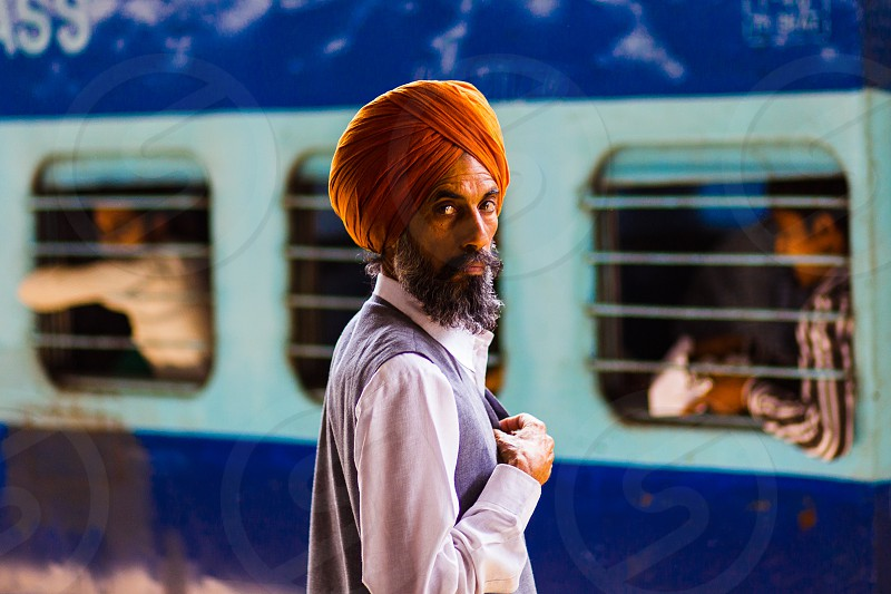 A portrait of a man in a train station in New Delhi India. He is wearing a bright orange turban and is framed in front of a bright blue and white train with passengers in the barred windows on each side of the man. photo
