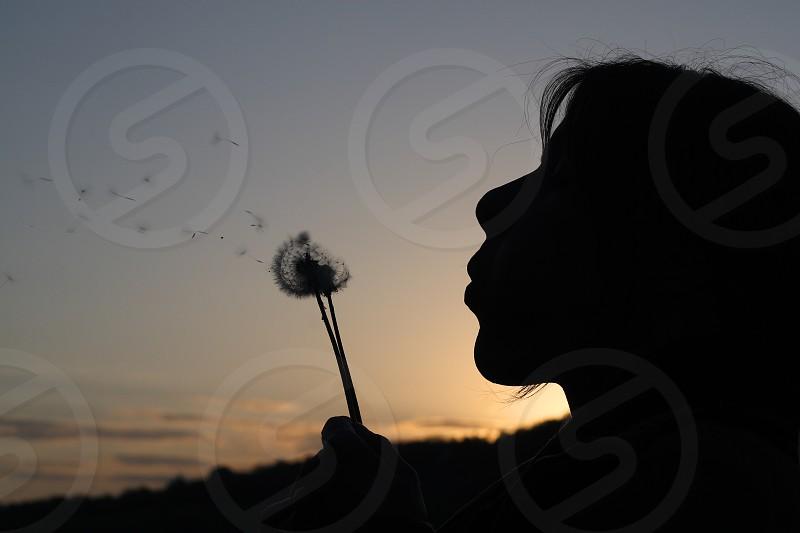 Woman blowing air at dandelion photo