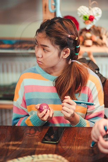 Young woman decorating the Easter eggs by scratching patterns on dyed eggs. Traditional Easter time spring time new beginnings. Candid people real moments authentic situations photo