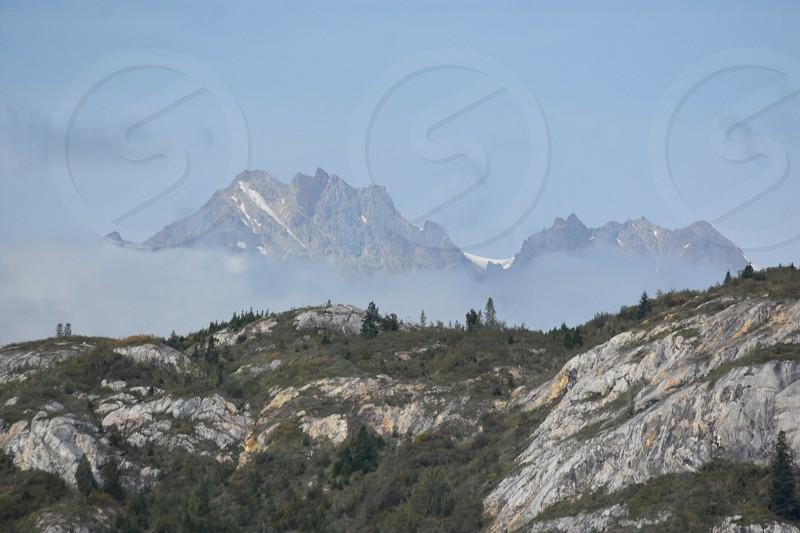 Fog amidst rocky mountains photo