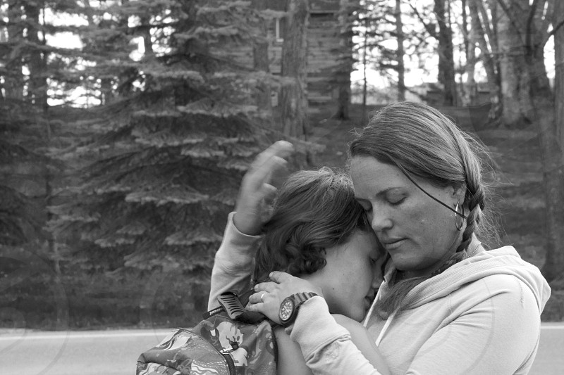 woman hugging a girl in grayscale photography photo