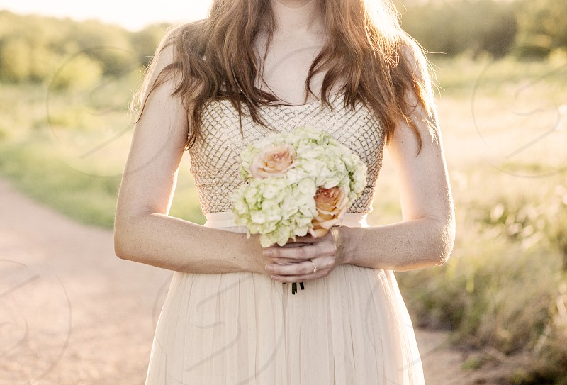 A woman holding a bouquet of flowers.  photo