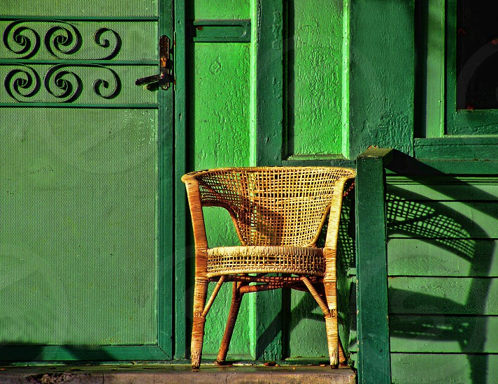 A yellow wicker chair is on the top step of a bright green house  photo