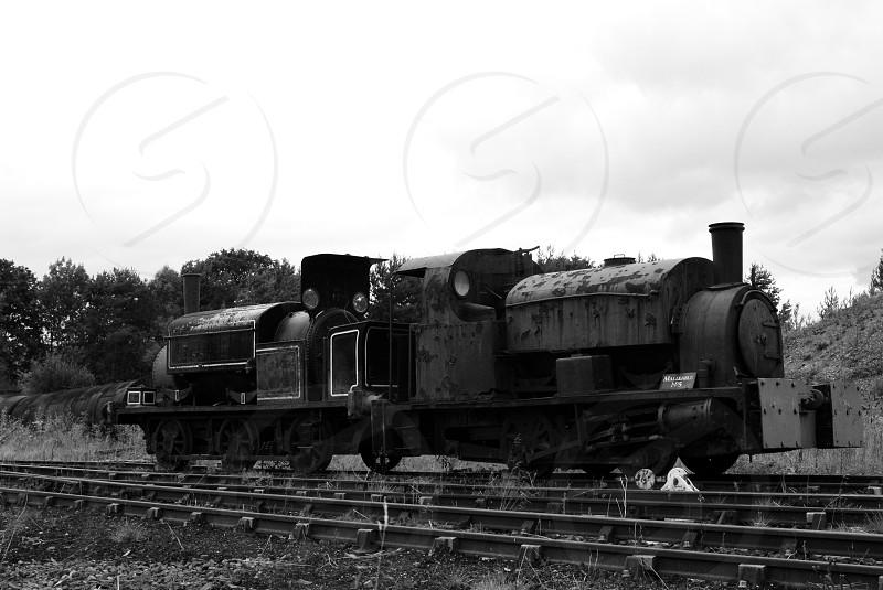 An old steam train on railway tracks photo