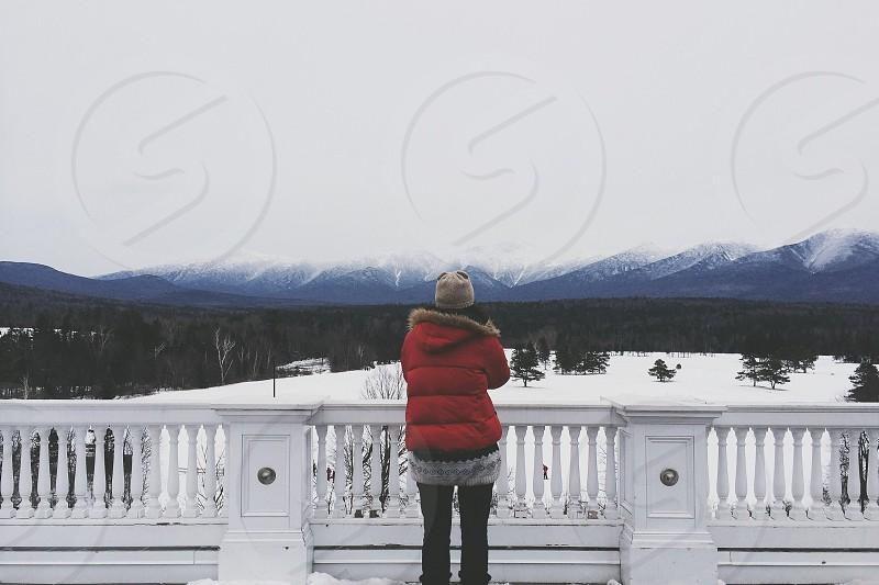 person in red winter coat at the veranda photo
