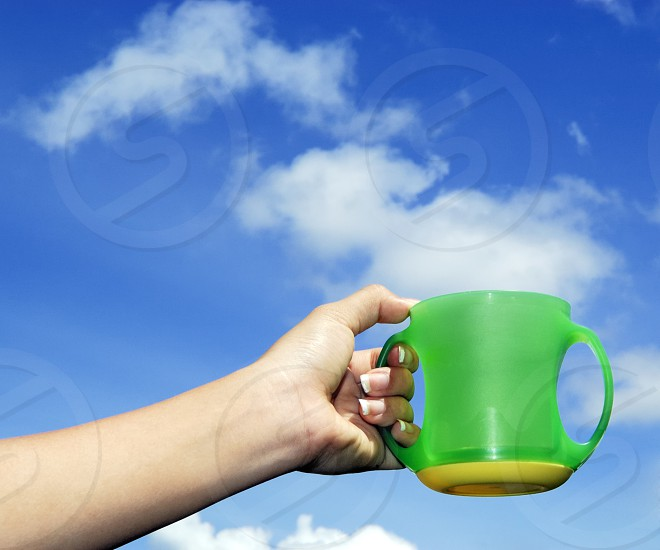 Closeup of hand holding cup against blue sky and clouds. photo