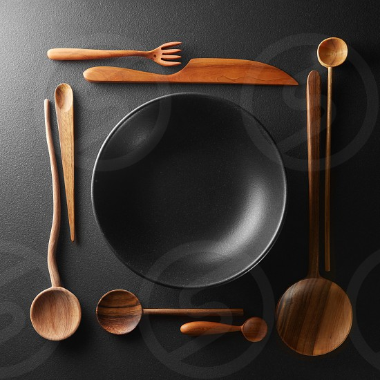 frame of setting empty black plate and wooden spoon fork knife on a black table. photo