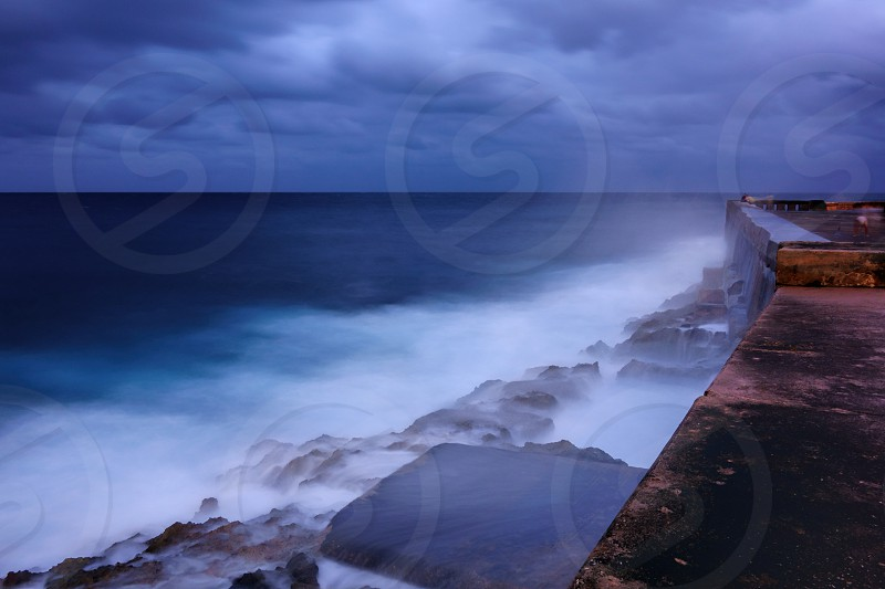 Evening by the walls of the Malecon esplanade in Havana Cuba and dramatic sea bounding water on the rocks. photo