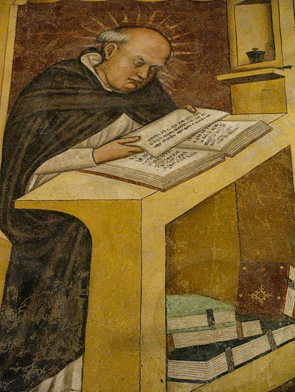 A tonsured monk with a halo reading a text is depicted in a Renaissance fresco in the monastery of the 13th Century church of San Nicolo in Treviso Italy. photo