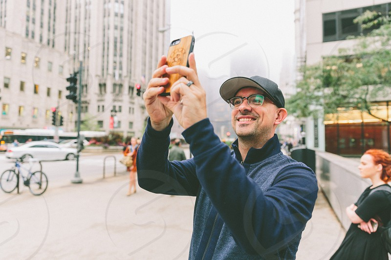 A man taking a photograph on a city street. photo