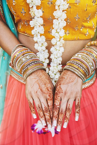 Close-up shot of Indian bride with beautiful sari in yellow blouse and red lehenga showing back hand with henna tattoo (mehndi) with a lot of glitter bracelets (bangles) on her wrist photo