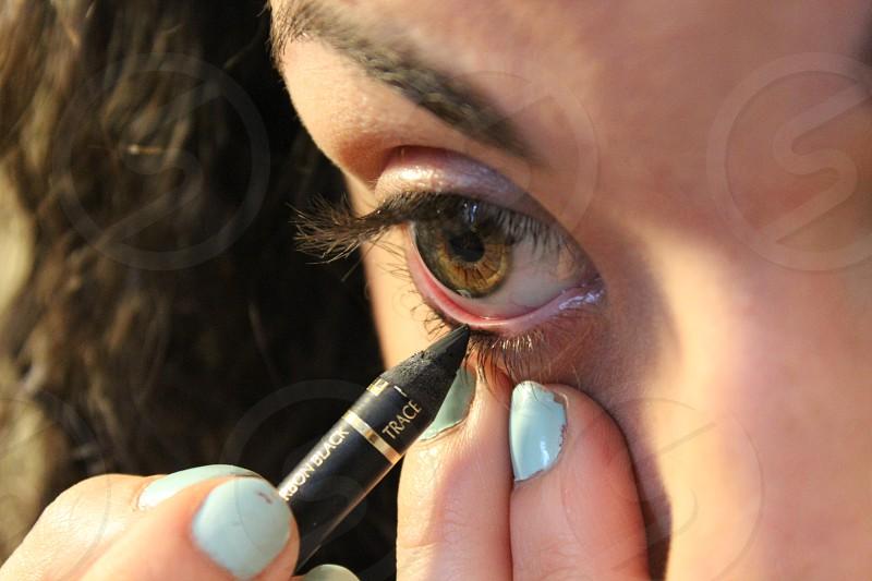 woman applying eyeliner on her eye photo