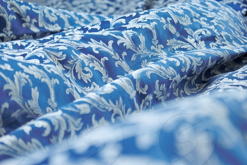 Beautiful blue classic-patterned bedclothes shot in bright light. photo