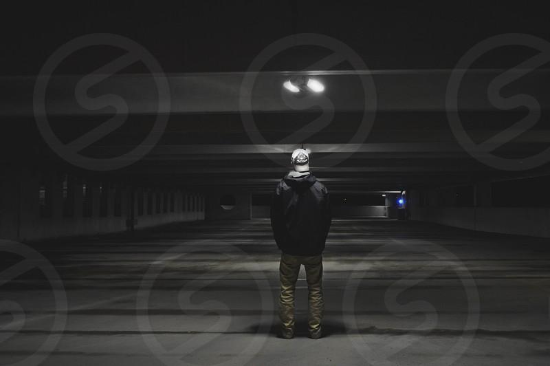 man standing in an empty parking garage photo