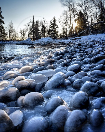 Round rocks covered in ice on beach with sun flare  photo