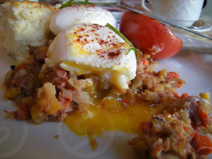 Burst yolk poached eggs over corned beef breakfast photo