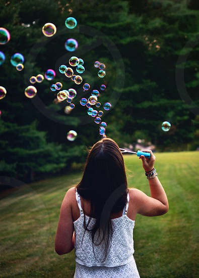 Girl faceless blowing bubbles photo