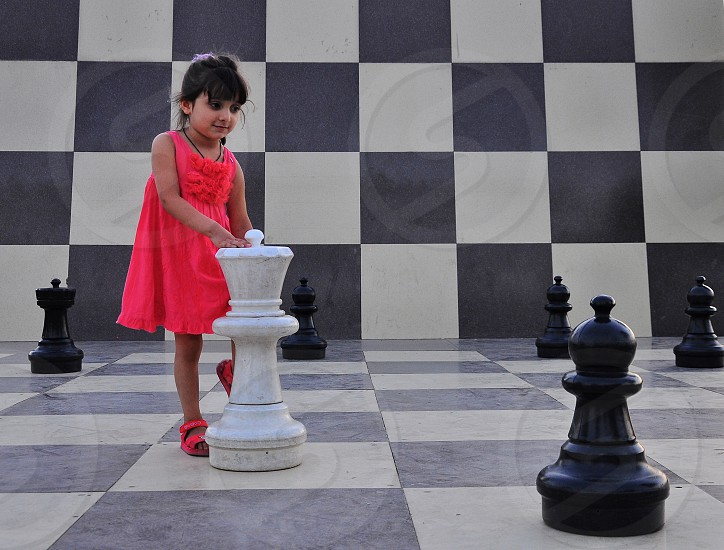 girl in coral dress moving large life size chess pieces photo